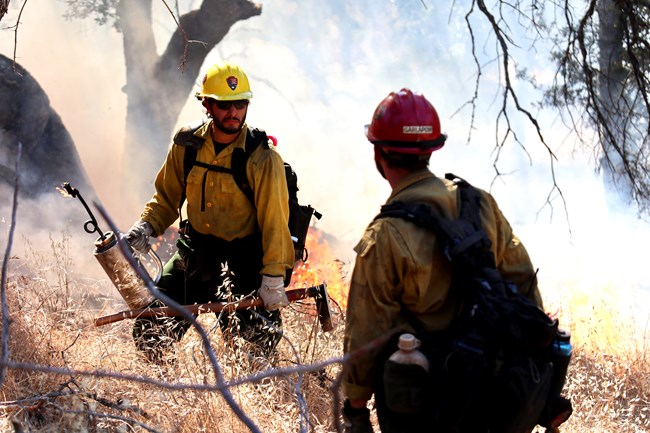 Firefighters communicate with each other during a grassland prescribed burn.