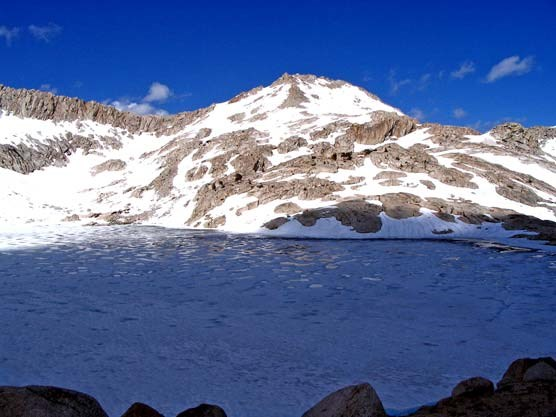 Frozen Columbine Lake with Sawtooth Mountain behind it