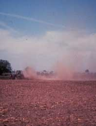 Farm tractor plowing field with dust billowing behind