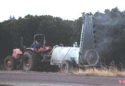 Tractor-pulled sprayer applying pesticides to citrus groves in the Central Valley of California