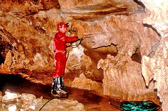 Cave specialist in red suit sprays water to clean a cave formation