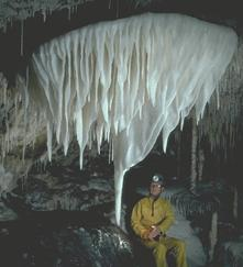 Visitor views a large white shield formation in the ceiling of Hurricane Crawl Cave in Sequoia and Kings Canyon National Parks