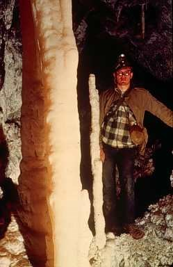 Man stands beside a clean Soldier Cave formation as it was in 1950