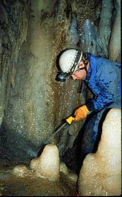 Volunteer helping clean muddied formation in Soldiers Cave