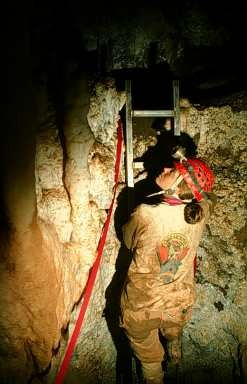 Cave specialist climbs ladder next to protective red flagging tape on the Column Pit in Soldiers Cave