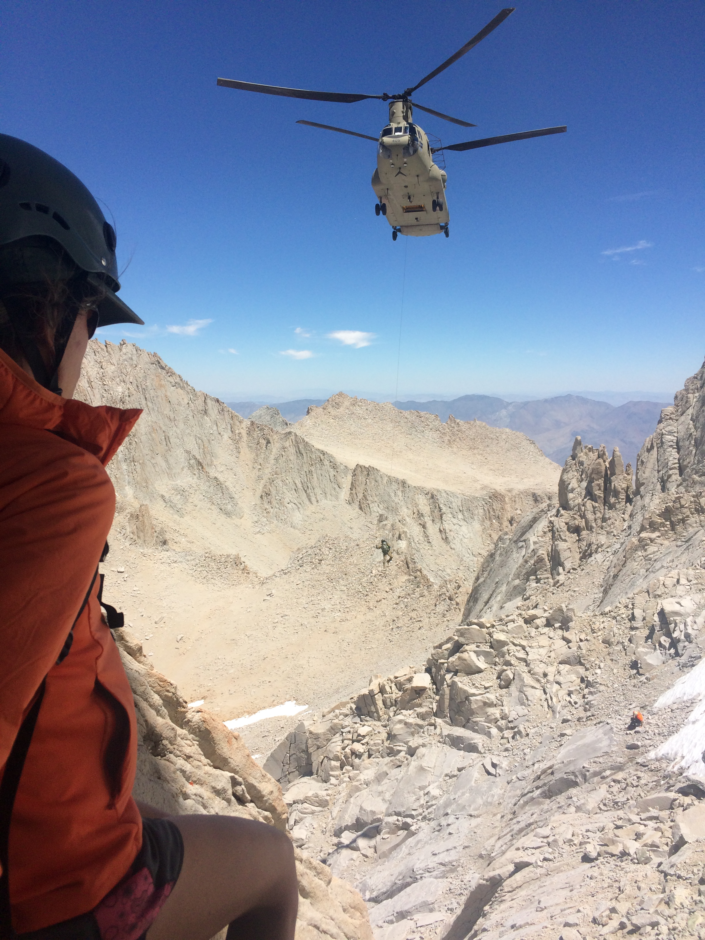 The search for missing hiker John Lee continues. This photo shows a searcher on a mountain in the foreground and a helicopter flying in the background. Photo courtesy of Inyo County Search and Rescue.