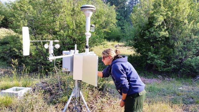 Ariane Sarzotti works with a portable particulate monitoring station known as an E-BAM to measure impacts from smoke caused by area fires. (Photo: NPS / Mike Theune)