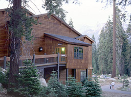 A wooden two-story building surrounded by conifers