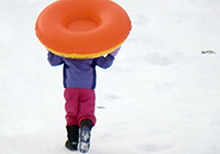 A child carries a sledding tube up a snowy hill