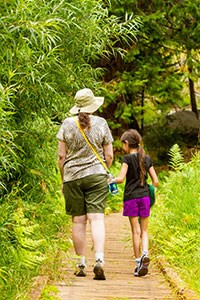 A woman and child walk along a wooden boardwalk in a lush meadow.