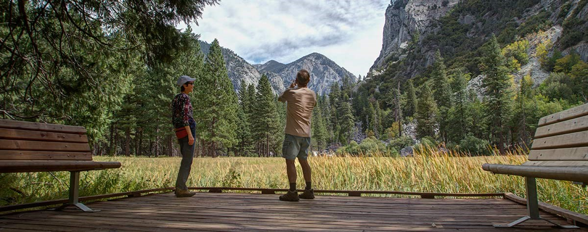 Two hikers pause for a photo on a boardwalk next to a meadow