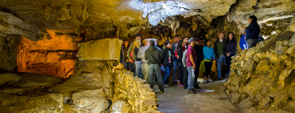 People gather in an open room along a cave trail