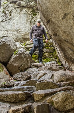 A man walks down a steep stone stairway