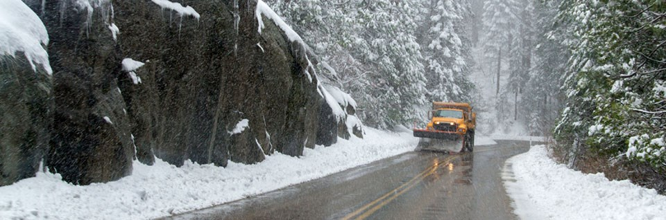 A snowplow drives along a snowy road