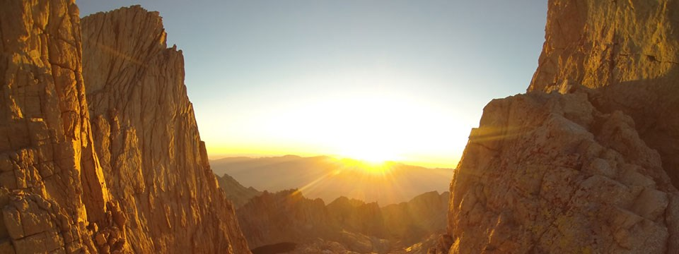 A sunrise lights up rocky peaks