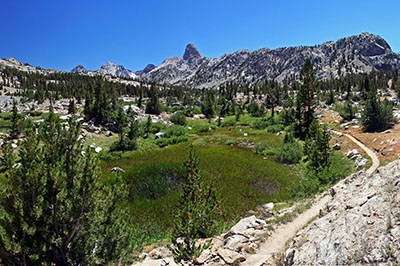 A trail leads past an alpine meadow surrounded by granite mountains