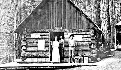 "Historic photo of log-cabin post office with park ranger and others standing in front. Sign above door reads ""Ranger Post Office."" NPS Photo"