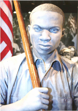 Image of a Sculpture of a marcher carrying an American flag.