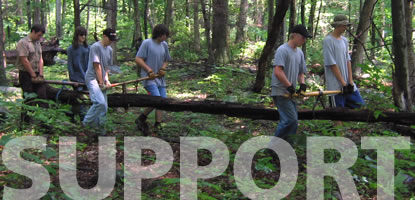 A group of volunteers move a fallen tree from a trail.