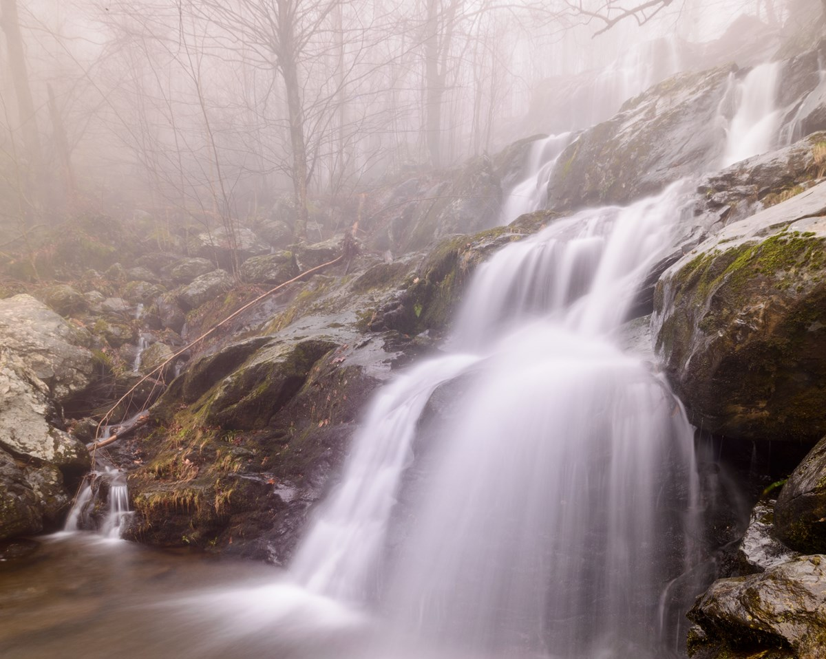 A cascading waterfall during autumn surrounded by fog.