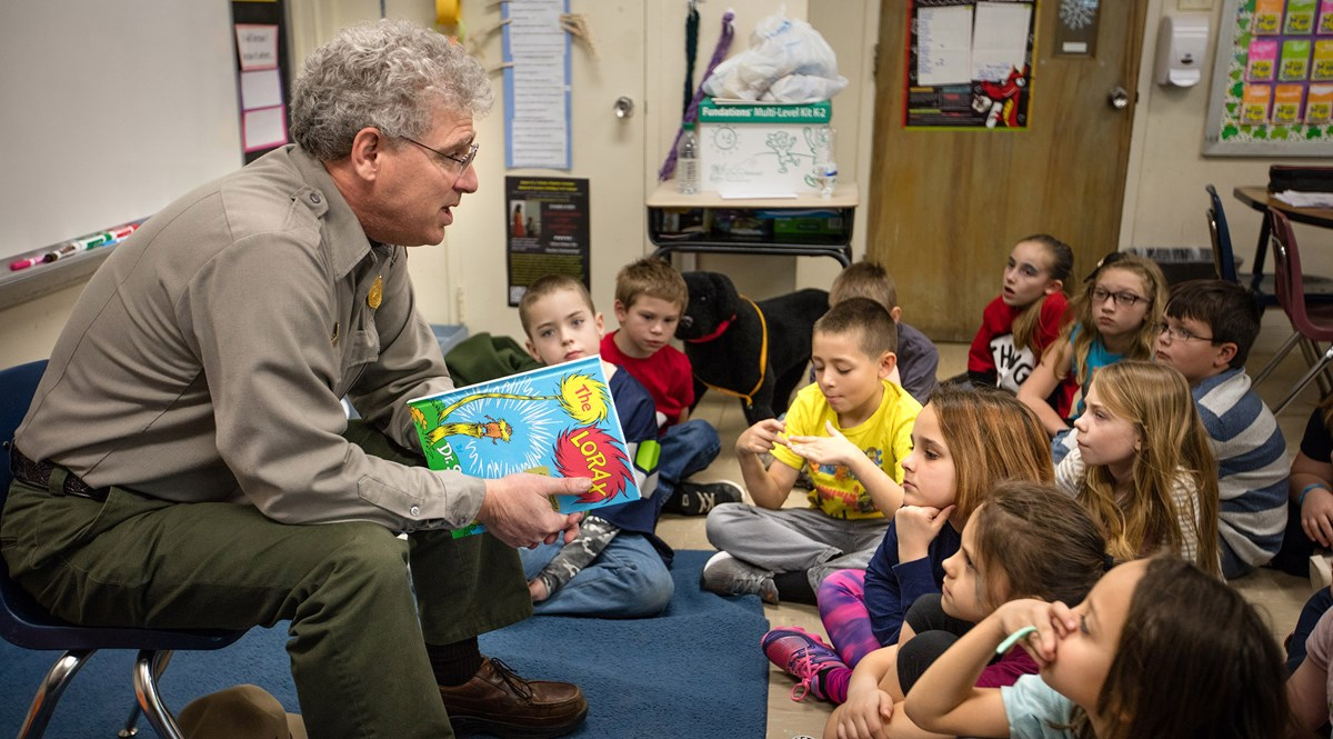 A ranger in a classroom reading to students