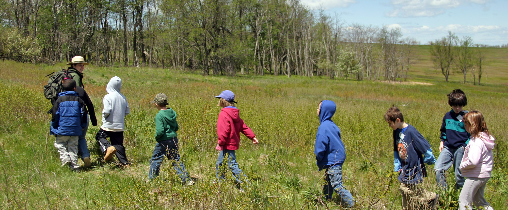 A Ranger leading a group of students through a meadow.