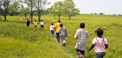 A ranger leads a group of young students across Big Meadows.