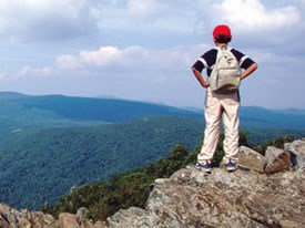A young boy stands on the rocky top of Hawksbill mountain and takes in a great view.