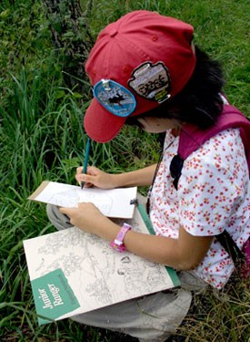 A young visitor wearing a red Junior Ranger hat and patches, sits in the grass of Big Meadows working on her Junior Ranger book.