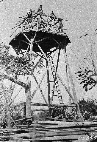 Historic black & white photo of Civilian Conservation enrollees constructing a fire tower.
