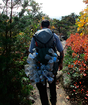 Park ranger removing trash collected on Old Rag; carrying a backpack full of plastic bottles.