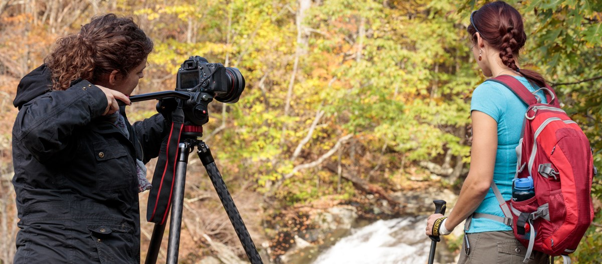 A videographer films a hiker posing for the camera in front of a landscape of fall color.