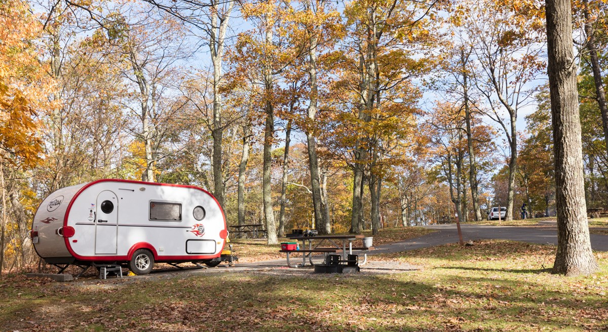 A red and white camper is parked under green trees in a campground.