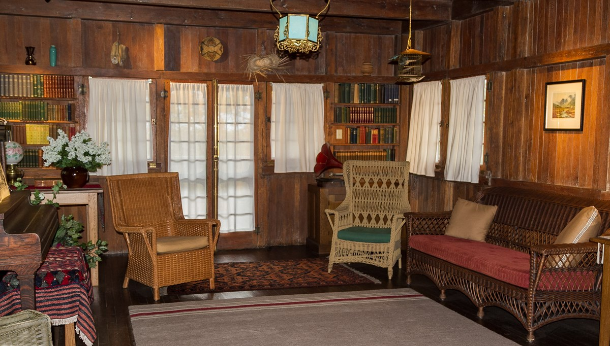 an interior room with hardwood and seating areas with historic furnishings.
