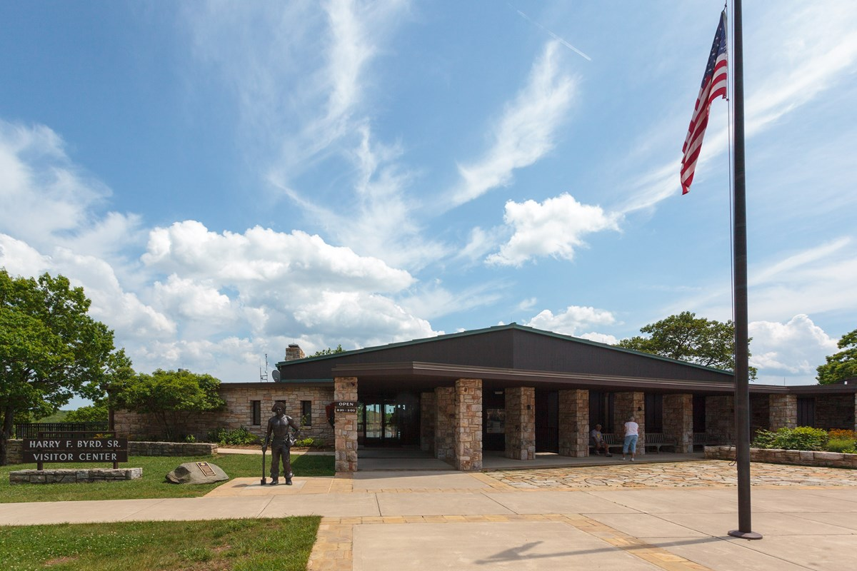 A stone building with glass doors and an American flag outside.