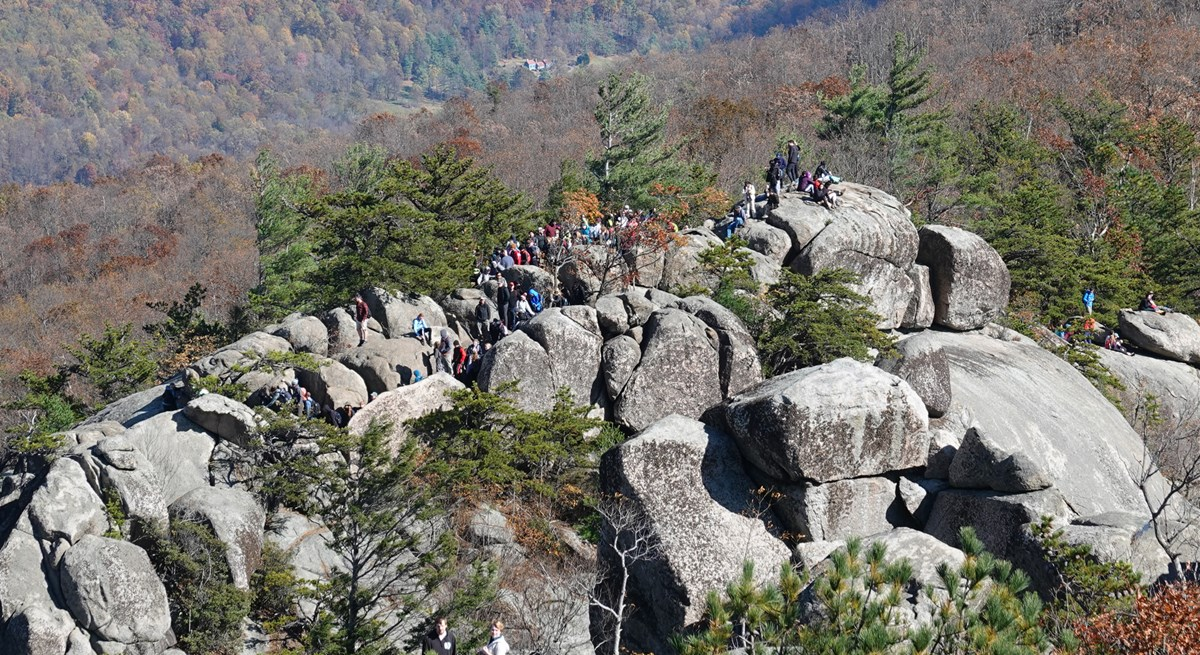A large crowd of hikers walk along the rocky ridge of a mountain.