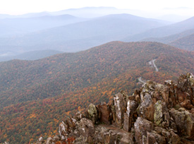 Rock outcrop of columnar jointing in the foreground with fall color explosion beyond.
