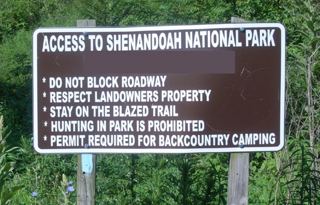 Brown sign with white lettering instructing visitors to stay on the trail