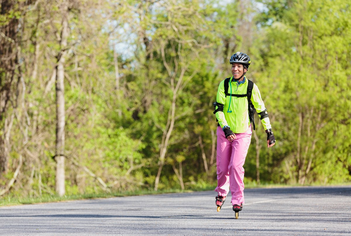 A color photograph of a woman rollerblading on the road.