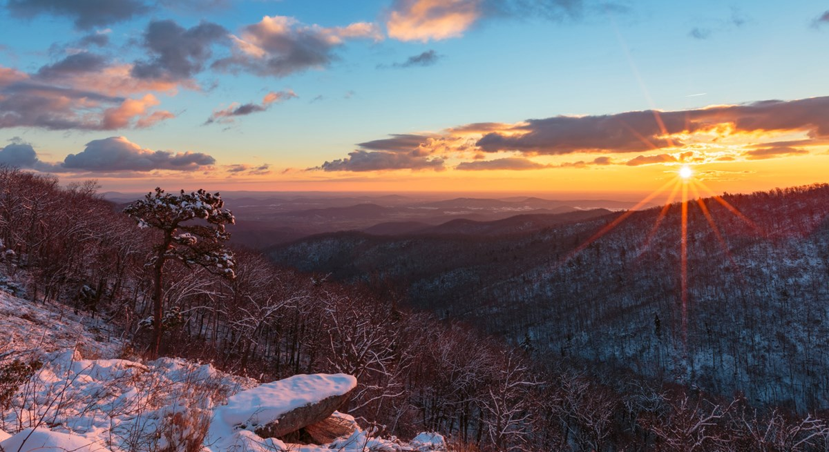 A sunrise over a mountain overlook filled with snow-covered rocks and trees