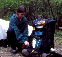 A backcountry camper sets up her campsite.