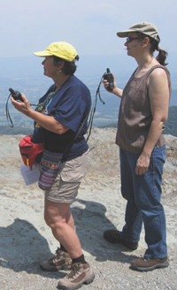 Two female hikers at the summit of Hawksbill study their GPS units.