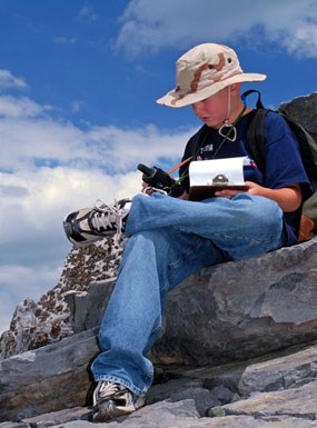 A young visitor sits on the rocks to study his GPS Unit while EarthCaching.