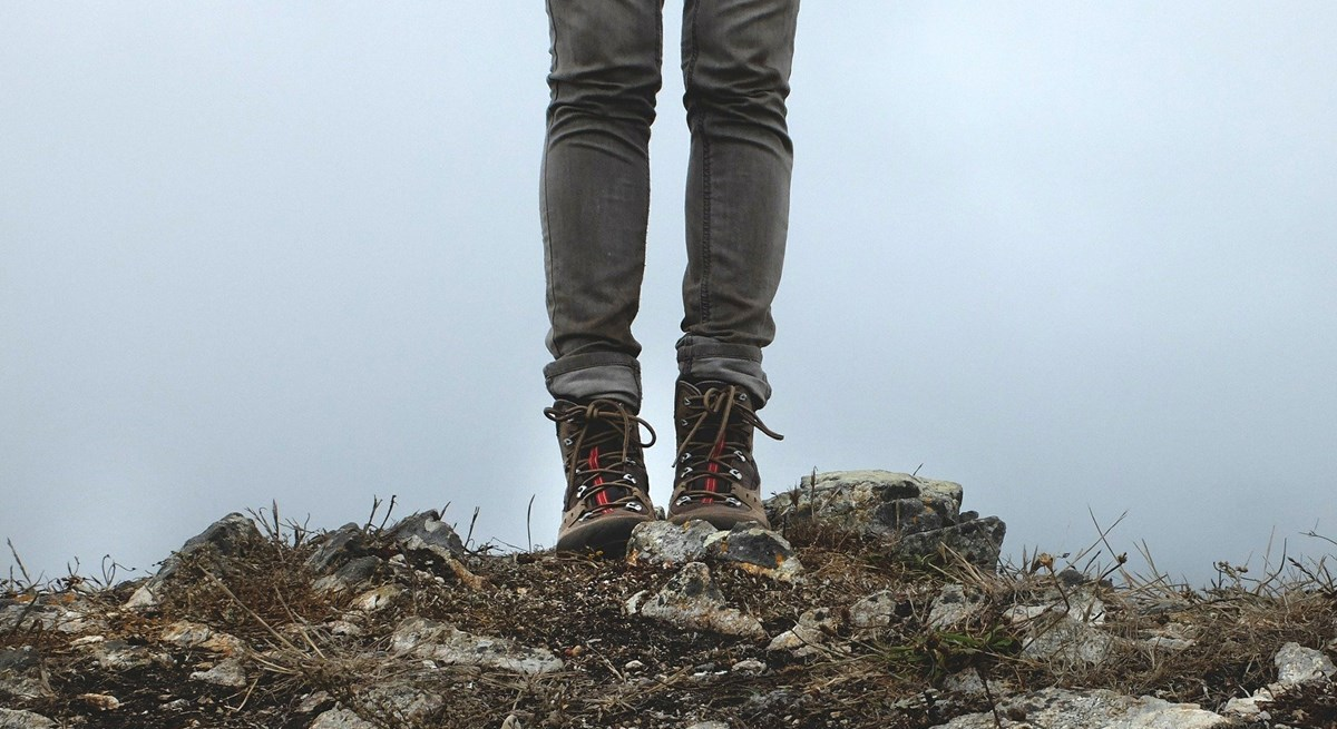 A close up of hiking boots standing on rocks in front of a cloudy viewpoint