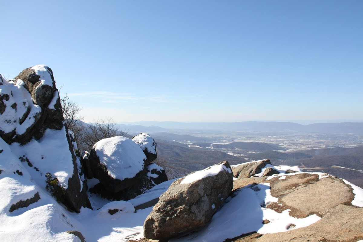 A view over a rocky mountaintop with snow and a clear sky.