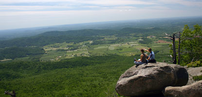 Two visitors catch a wondrous view of the Shenandoah Valley from a rocky ledge in Shenandoah.