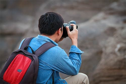 A man holding a camera with a blurred background.