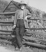 Historic photo of older gentleman in hat with long white beard leaning against a split rail fence.