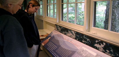 Visitors read informative exhibit panels at historic Rapidan Camp.