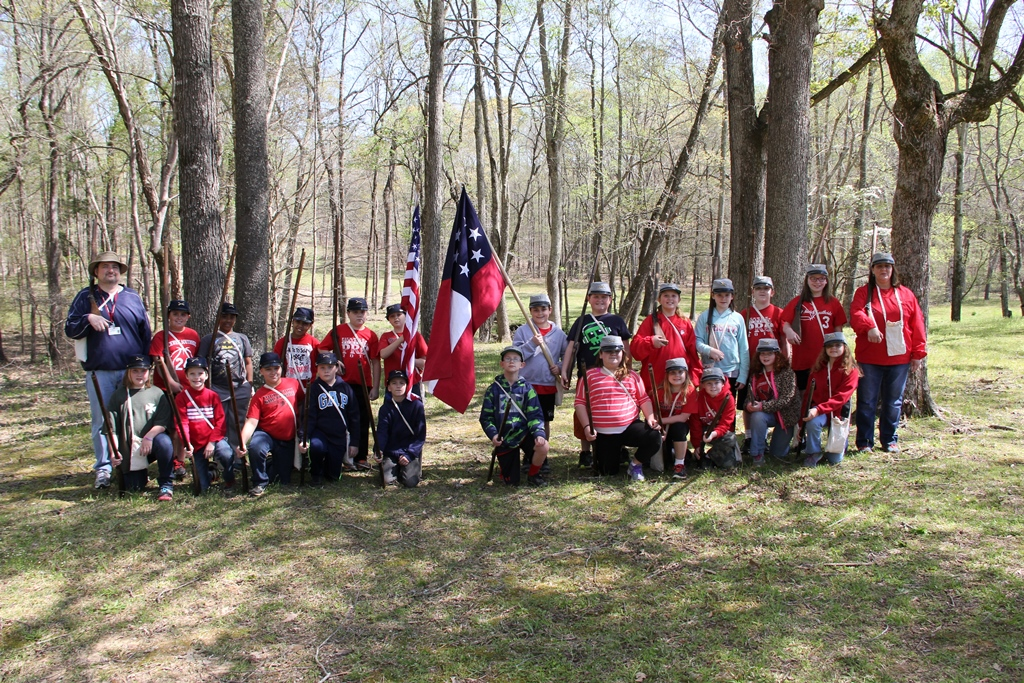 Kids posing holding flags and muskets